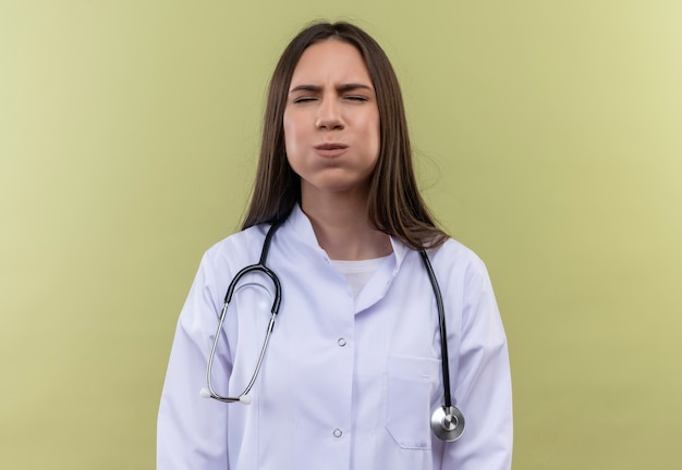 Jong artsenmeisje dat stethoscoop medische toga draagt - op groene muur