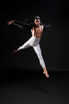 Jong atletisch mannetje dat en op zwarte achtergrond springt danst