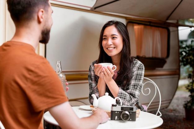 Jong avontuurlijk stel met een kopje thee buitenshuis