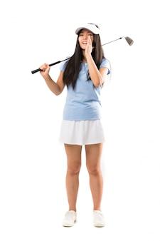 Jong aziatisch golfspelermeisje over geïsoleerde witte muur die met wijd open mond schreeuwen