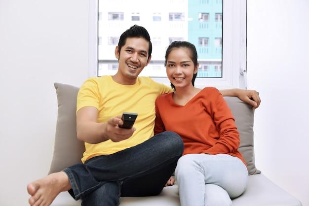 Jong aziatisch houdend van paar die en op televisie ontspannen letten