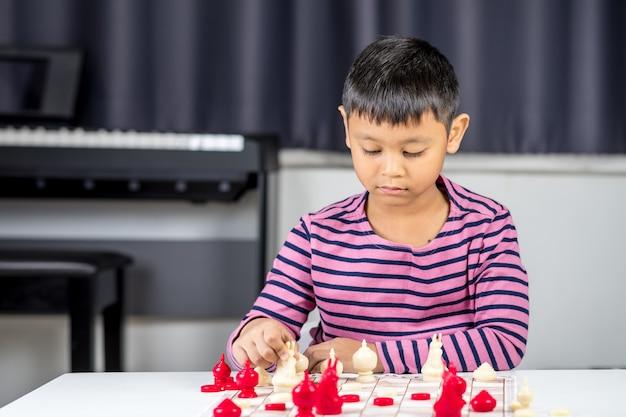 Jong aziatisch jongens speelschaak in de ruimte