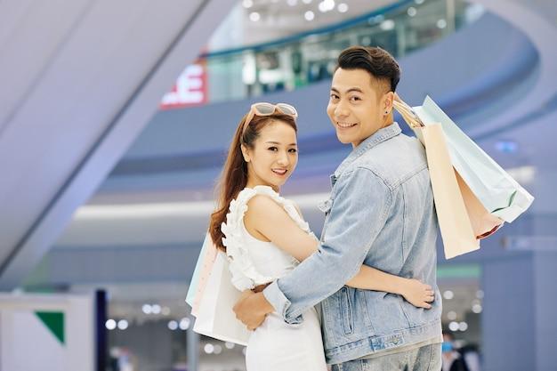 Jong aziatisch koppel knuffelen met boodschappentassen staan in winkelcentrum, draaien terug en glimlachen aan de voorkant
