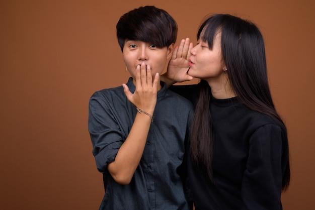 Jong aziatisch lesbisch paar samen en verliefd tegen bruin