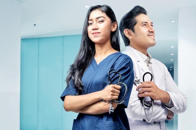 Jong aziatisch medisch personeel die zich rijtjes met holdingsstethoscoop bevinden