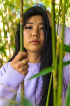 Jong aziatisch meisje binnen enkele prachtige bamboe in een park. terugtrekking van een jonge brunette met een roze trui van chinese nationaliteit, aziatische etniciteit