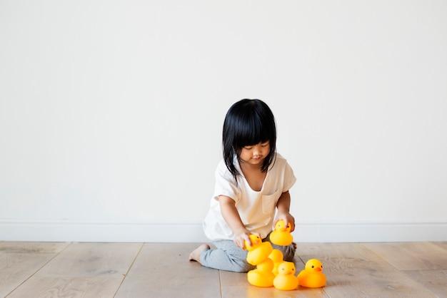 Jong aziatisch meisje dat alleen speelt