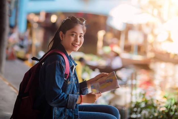 Jong aziatisch meisje dat bij de drijvende markt van dumonoe saduak, thailand loopt