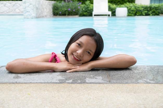 Jong aziatisch meisje dat bij zwembad glimlacht.