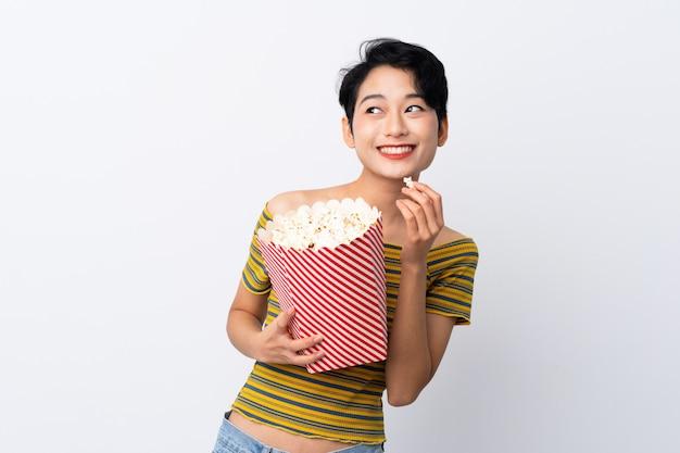 Jong aziatisch meisje dat een grote emmer popcorns houdt