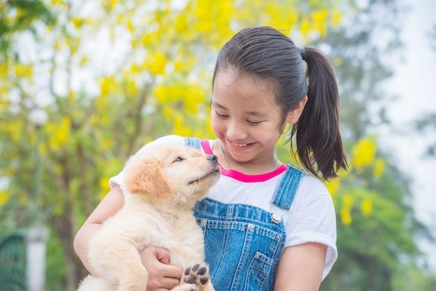 Jong aziatisch meisje dat een kleine golden retrieverhond in park houdt