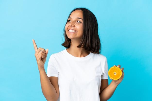 Jong aziatisch meisje dat een sinaasappel houdt die op blauwe achtergrond wordt geïsoleerd die een geweldig idee benadrukt