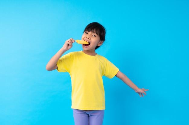 Jong aziatisch meisje dat geel roomijs op blauw eet