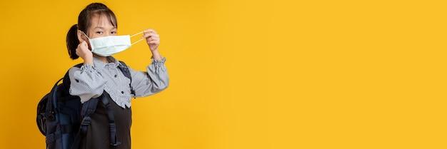 Jong aziatisch meisje dat gezichtsmasker in studio op geel draagt