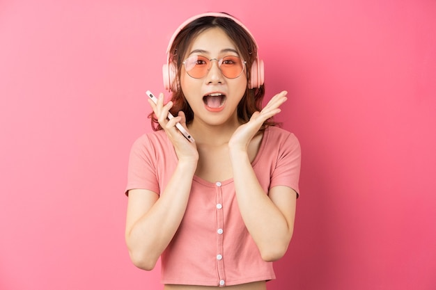 Jong aziatisch meisje dat hoofdtelefoons draagt en de telefoon op roze gebruikt