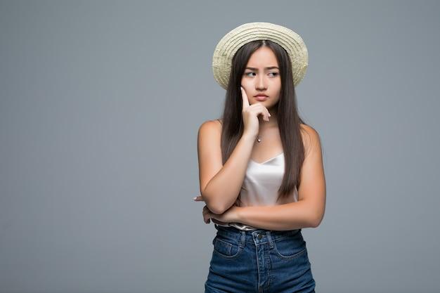 Jong aziatisch meisje dat in strohoed iets op grijze achtergrond denkt