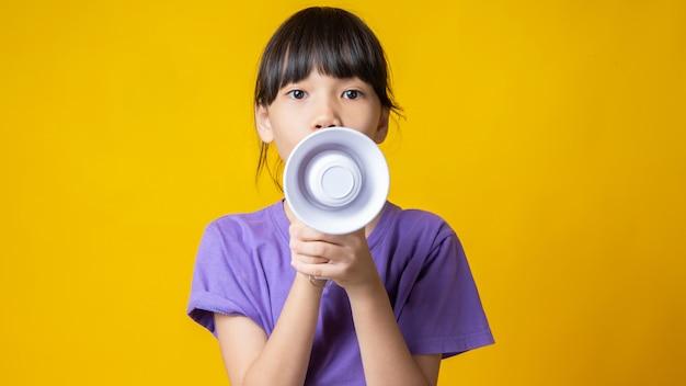 Jong aziatisch meisje dat in violet overhemd witte megafoon houdt om te schreeuwen