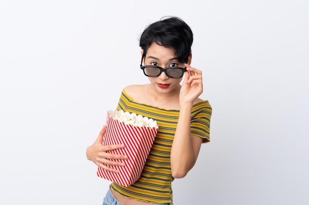 Jong aziatisch meisje dat met glazen wordt verrast en een grote emmer popcorns houdt