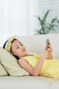 Jong aziatisch meisje dat op bank ligt thuis en smartphone gebruikt