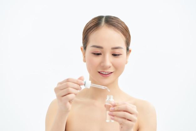 Jong aziatisch meisje dat serum of huidverzorgingsproduct op haar gezicht aanbrengt. geïsoleerd op een witte achtergrond.