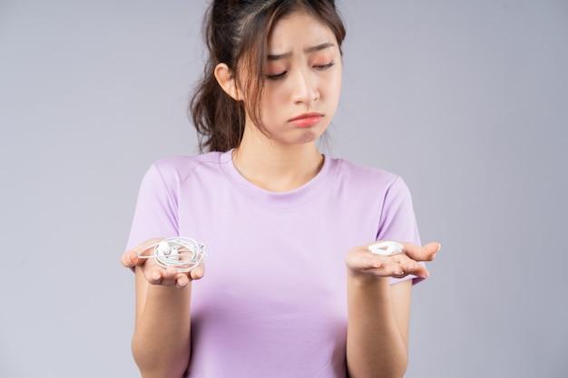 Jong aziatisch meisje dat tussen bedrade hoofdtelefoons en draadloze hoofdtelefoons in verwarring wordt gebracht