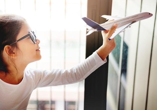 Jong aziatisch meisje dat vliegend vliegtuigspeelgoed speelt