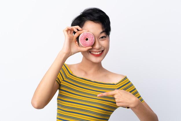 Jong aziatisch meisje die een doughnut houden en gelukkig