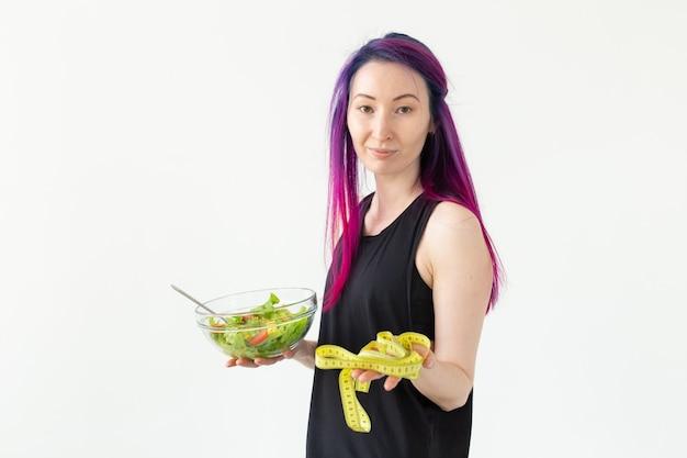 Jong aziatisch meisje hipster gekleurd haar met in handen een meetlint en groentesalade poseren