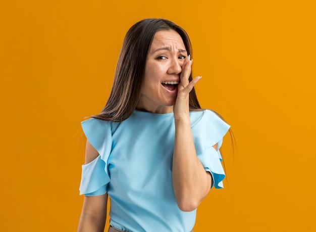 Jong aziatisch meisje houdt hand op gezicht schreeuwend kijkend naar camera geïsoleerd op oranje muur met kopieerruimte