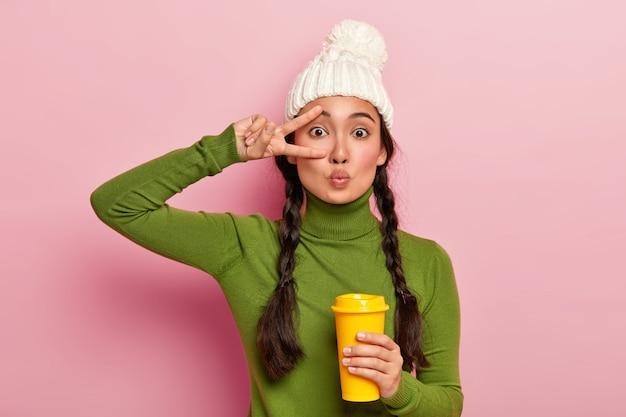 Jong aziatisch meisje houdt lippen gevouwen, maakt vredesgebaar, draagt witte warme wintermuts, groene trui, geniet van koffie om mee te nemen, staat tegen roze muur