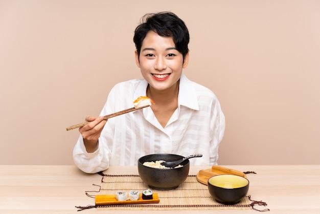 Jong aziatisch meisje in een lijst met kom van noedels en sushi