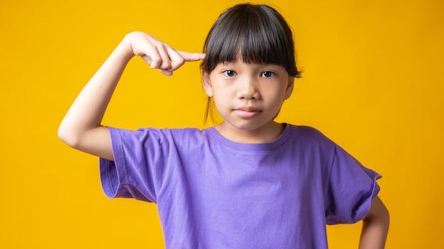 Jong aziatisch meisje in violet overhemd denken en wijzen naar het hoofd om een idee te krijgen,