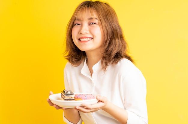 Jong aziatisch meisje met een bord cake met een vrolijke uitdrukking