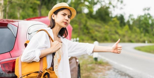 Jong aziatisch meisje met een rugzak die om hulp vraagt omdat de auto kapot is tijdens het reizen op vakantie.