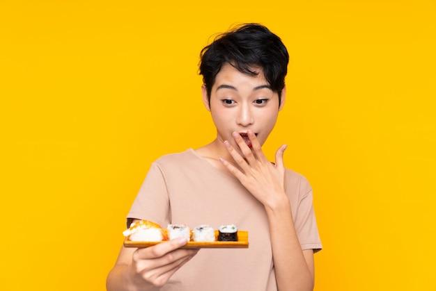 Jong aziatisch meisje met sushi met verrassing en geschokte gelaatsuitdrukking