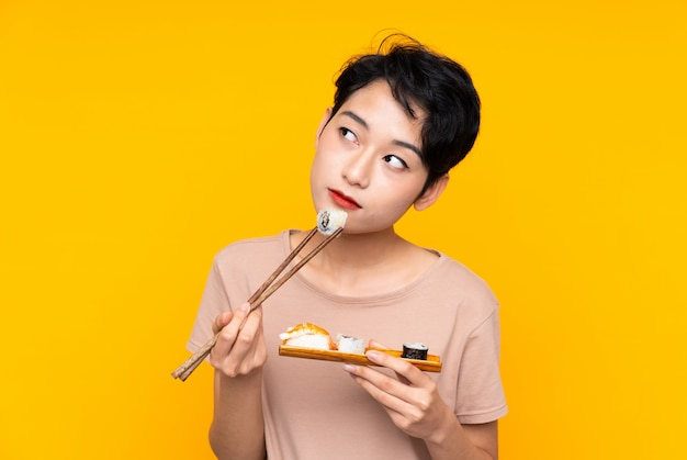 Jong aziatisch meisje met sushi over gele muur
