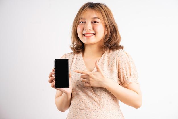 Jong aziatisch meisje met telefoon met uitdrukkingen en gebaren op wit