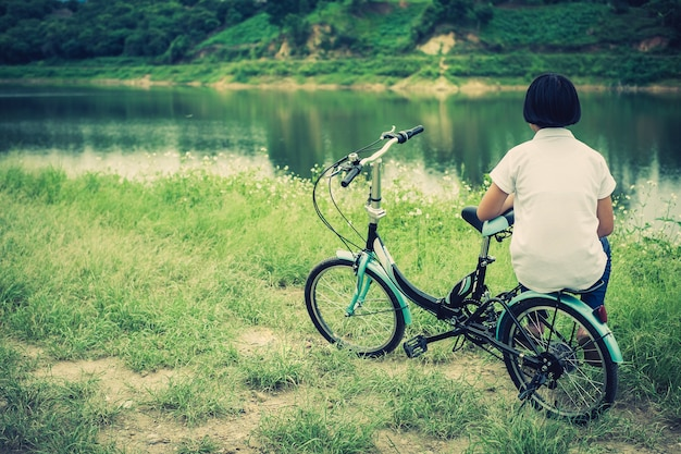 Jong aziatisch meisje met uitstekende fiets in het landschap van de plattelandsaard.