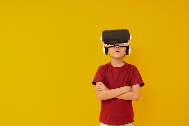 Jong aziatisch meisje met virtuele werkelijkheidsglazen, jong geitje wauw en het verlaten met vr-presentatie op geel