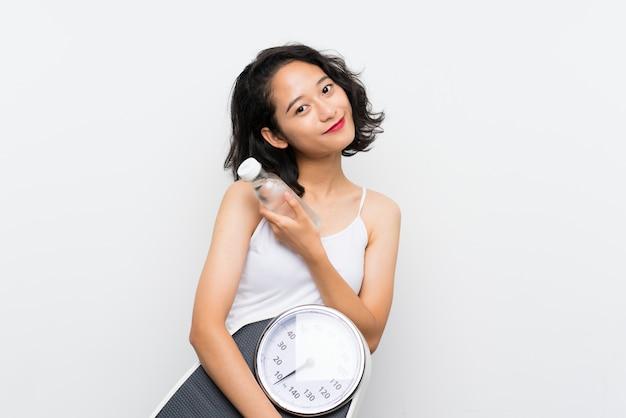 Jong aziatisch meisje met weegmachine over geïsoleerde witte muur