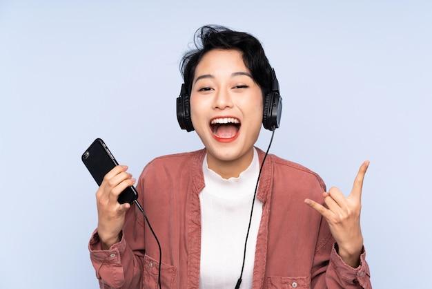 Jong aziatisch meisje over geïsoleerde blauwe muur het luisteren muziek die rotsgebaar maken