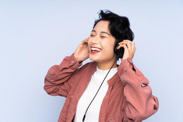 Jong aziatisch meisje over geïsoleerde blauwe muur het luisteren muziek en het zingen