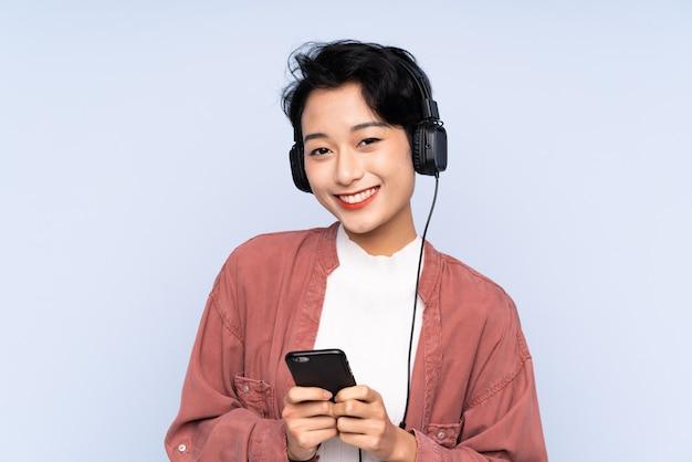 Jong aziatisch meisje over geïsoleerde blauwe muur het luisteren muziek met mobiel en het kijken voorzijde
