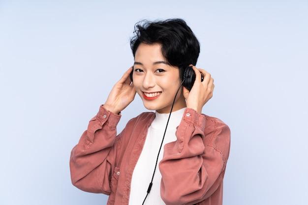 Jong aziatisch meisje over geïsoleerde blauwe muur het luisteren muziek