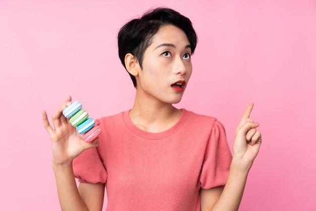 Jong aziatisch meisje over geïsoleerde roze muur die kleurrijke franse macarons houden en van plan zijn om de oplossing te realiseren
