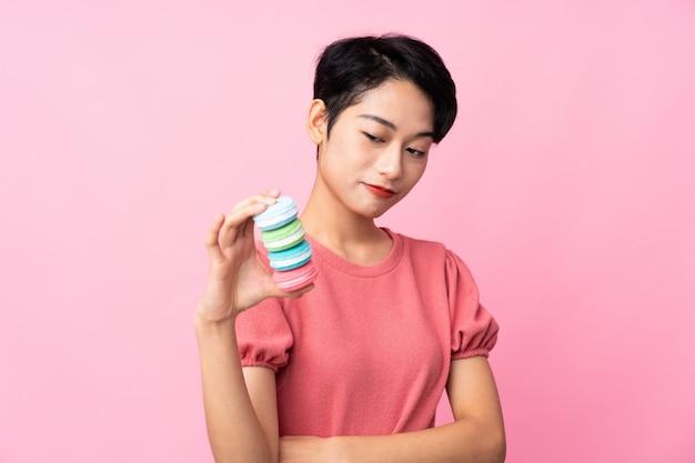 Jong aziatisch meisje over geïsoleerde roze muur die kleurrijke franse macarons met droevige uitdrukking houden