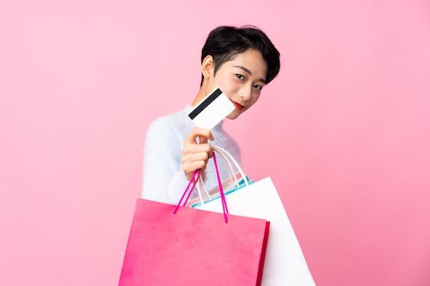 Jong aziatisch meisje over geïsoleerde roze muurholding het winkelen zakken en een creditcard
