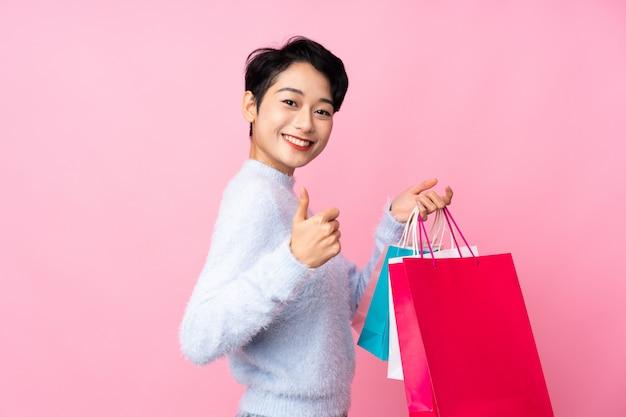 Jong aziatisch meisje over geïsoleerde roze muurholding het winkelen zakken en met omhoog duim