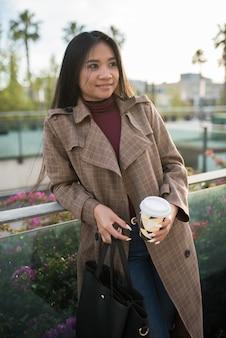 Jong aziatisch meisje wacht leunend op een reling met een kopje koffie in de ene hand en een portemonnee in de andere the