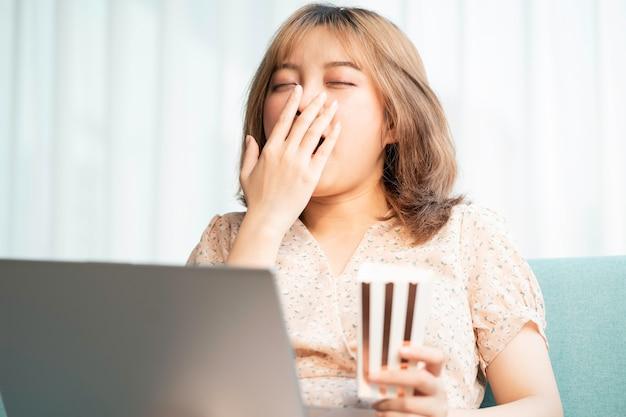Jong aziatisch meisje zittend op de bank eten en films kijken op laptop
